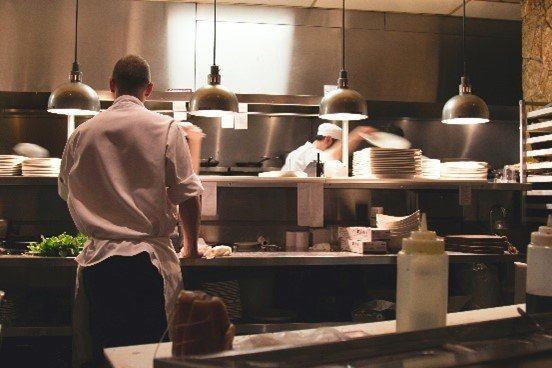 kitchen back end food prep station with chef and waiter