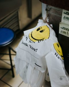 Plastic To-Go bag with a yellow smiley face and thank you written on it
