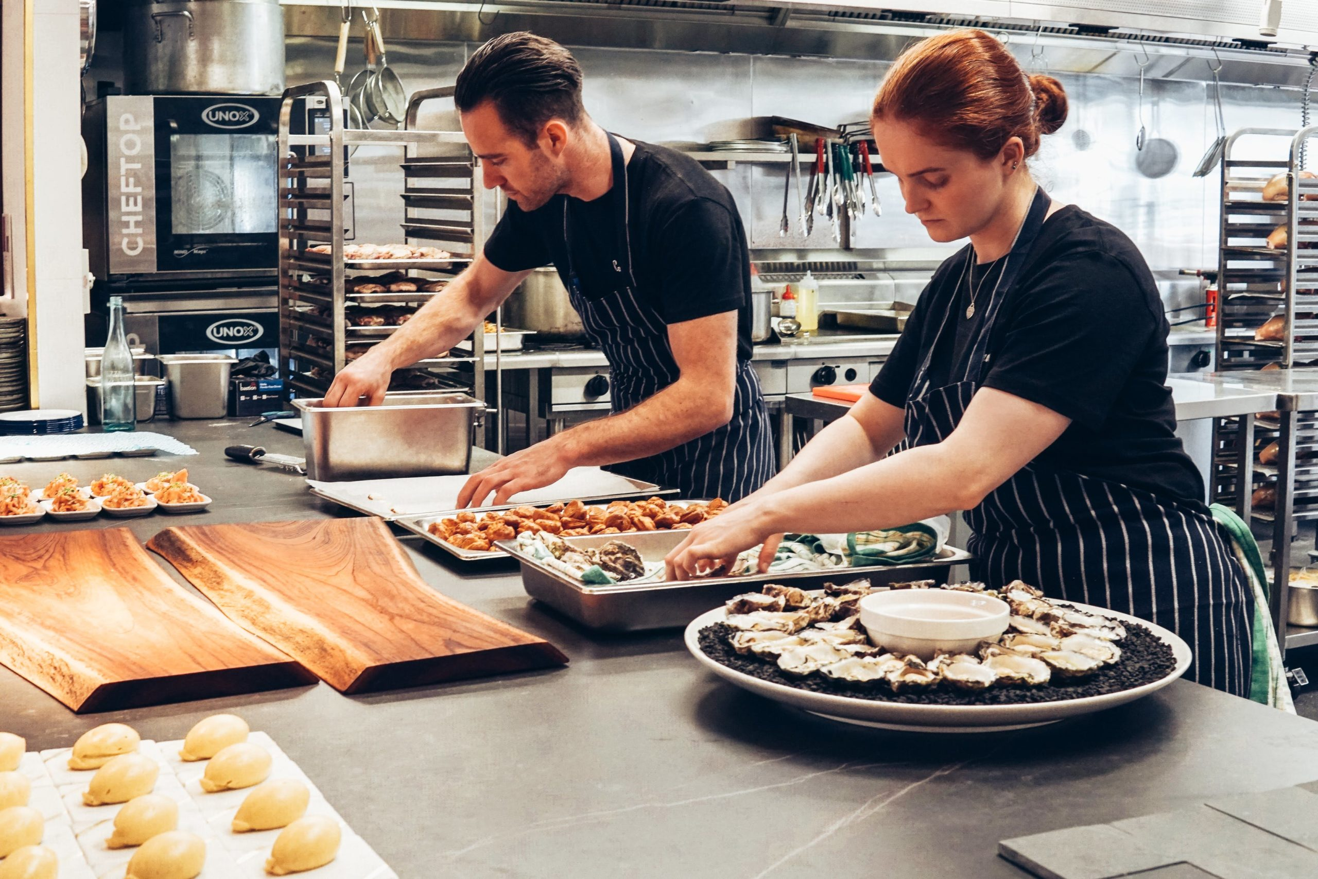 man and woman prepping food in the back end of the kitchen for a meal at a restaurant
