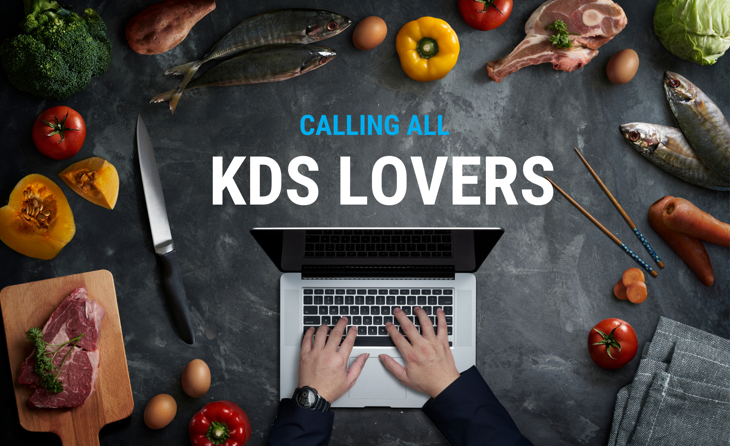 calling all KDS lovers on laptop surrounded by food and cooking utensils such as knives and a cutting board
